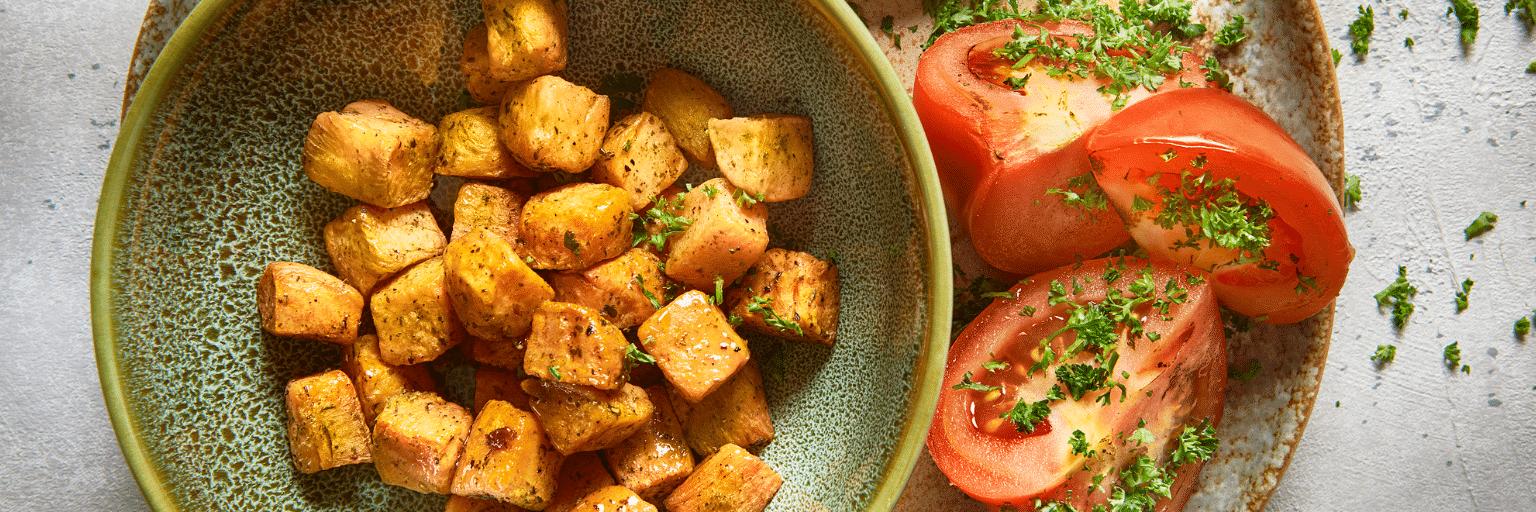 Zoete aardappel ovenschotel met lamsworstjes en gegrilde tomaat